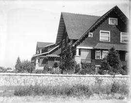 [Unidentified house with rock fence]