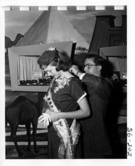 Miss P.N.E., Joan Greenwood, having necklace placed on her at Millers Jewelers display in Manufac...