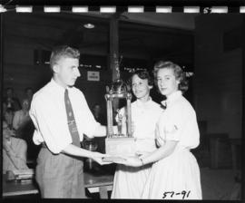 Girls receive trophy in 1957 P.N.E. 4-H and Future Farmers of Canada competition
