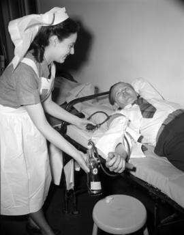 [Red Cross nurse attending a blood donor]