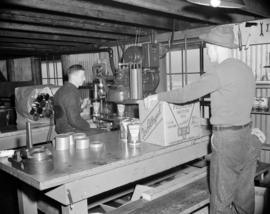 [B.A. Oil Company workers filling cans of Peerless oil and packaging them into boxes for shipment]