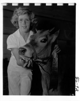 Girl with award-winning Jersey cow from 1956 P.N.E. 4-H and Future Farmers of Canada competition