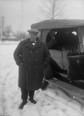 Man standing next to an automobile