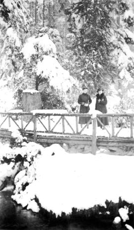Two women standing on a wooden bridge with lots of snow