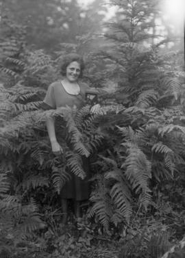 Woman with a camera standing amongst ferns
