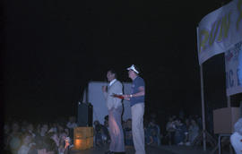 Two unidentified men on stage at night