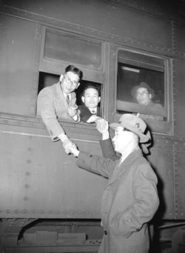 [Japanese evacuees shaking hands with friends through train windows at the CPR station en route t...