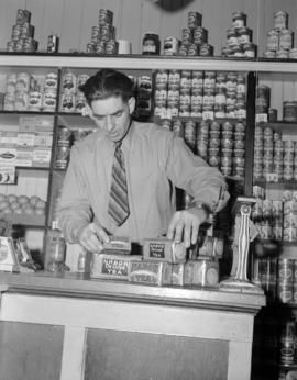 [Man setting up a Nabob tea display at a grocery store]