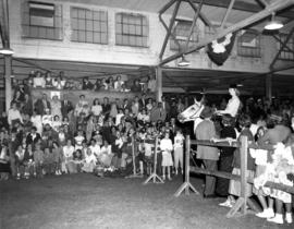 Woman riding horse as crowd watches in Livestock building