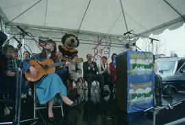 Megan Metcalfe with guitar on Chevron stage during Vancouver AM sign unveiling at Oak Street and ...