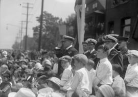 Military officers saluting in a crowd of boys