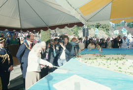 Jeanne Sauvé cutting Centennial birthday cake with ceremonial sword