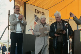 Mike Harcourt on stage with unidentified man and woman at Polar Bear Swim
