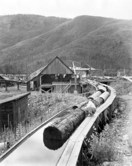 [Flume beside Sheep Creek River going into F.R. Rotter lumber mill]