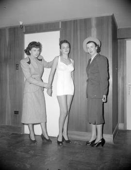 [Women standing with a bathing suit model]