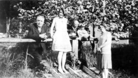 [Group portrait of L.D. Taylor with unidentified family in yard]