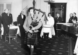 [A bagpiper proceeds the birthday cake at The Honourable E.W. Hamber's birthday dinner]