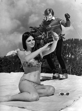 Linda Bindley sun tanning in swimsuit on Grouse Mountain with skier in background