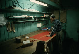 Wing Hing Dry Goods owner Lin Bei-lian working at the cloth cutting table inside his shop