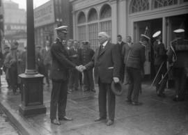 Man in uniform shaking hands with man in suit on the street