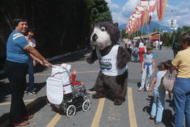 Tillicum greeting child in stroller at P.N.E. grounds