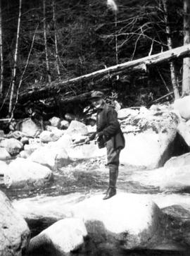 [Unidentified woman fishing while standing on large rock in river near Summit Lake]