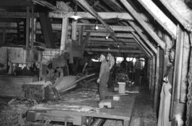 [Men and machinery at a sawmill]