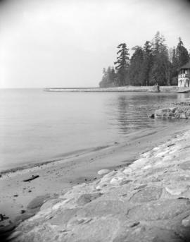 [View of Stanley Park seawall and a park building]