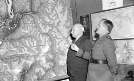 [Brigadier General Alex Ross and S.F.M. Moodie examining a large wall map]