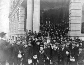 [Large group of boys with lunch bags standing in front of building]