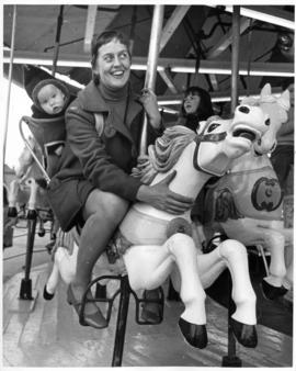 Nel Snyder riding merry-go-round at Playland