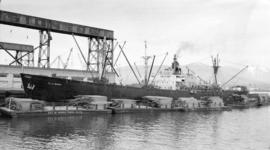S.S. Villa Marion [at dock, with lumber-filled barges alongside]