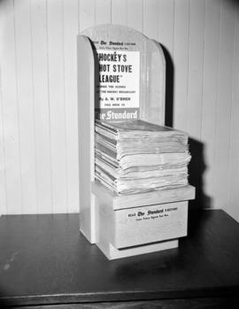 [Newspaper rack for 'The Standard']