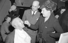 [Mr. Rowe Holland having makeup done by Don Brown and Mrs. T. Rolston for Theatre Under the Stars]