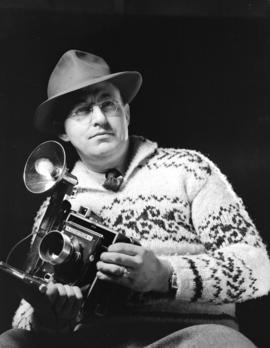 Don Coltman wearing Indian sweater [and holding a] camera