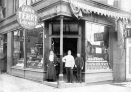 Bert A. Emery [standing with two other people in the entrance of Terry's Drug Store]
