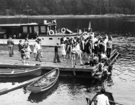 [Boaters and swimmers at recreational floating dock]
