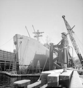 """Fort Mumford"" in drydock [being guarded by a soldier]"