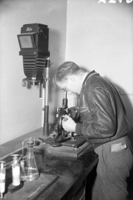 [Scientist making a metalurgic examination of a piece of metal at the University of British Colum...