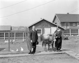 Detective and Mrs. McLaughlin in yard [1938 Wolfe Avenue] with chickens and cow