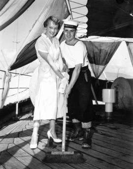 Miss P.N.E. contestant sweeping deck with sailor aboard the H.M.S. Sheffield