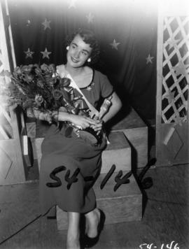 Winner of Miss P.N.E. 1954, Nancy Hansen of Burnaby, B.C. posing with roses and trophy