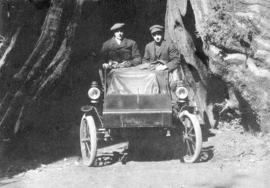 "[Alex and William Fenton in their ""Thomas"" car in front of the Hollow Tree]"