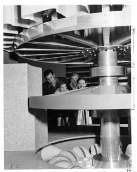 Family looking at water turbine in hydroelectricity exhibit in P.N.E. B.C. building