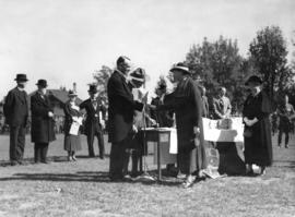 [His Worship G.G. McGeer presents Mrs. A.C. Bagley with a King's Jubilee Medal at Brockton Oval]