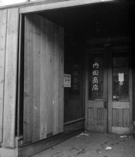 [Japanese store front boarded up showing a 'for rent' sign and Wartime Prices and Trade...
