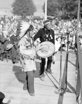 [August Jack Khatsahlano and another man playing music at the rededication of Stanley Park]