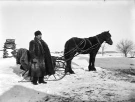[Man in fur coat and hat standing next to horse drawn sleigh]