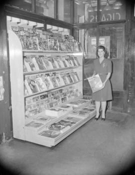[Woman holding a copy of the Saturday Evening Post by a magazine rack display in a store]