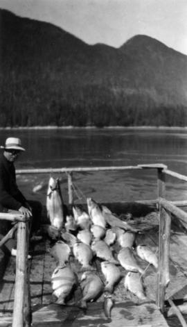 [L.D. Taylor sitting on a dock with caught salmon, Stuart Island, B.C.]